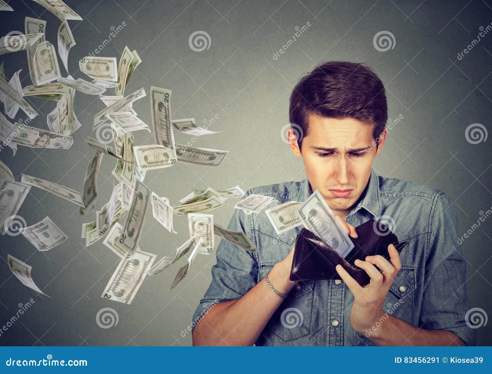 Sad man looking at wallet with money dollars flying away