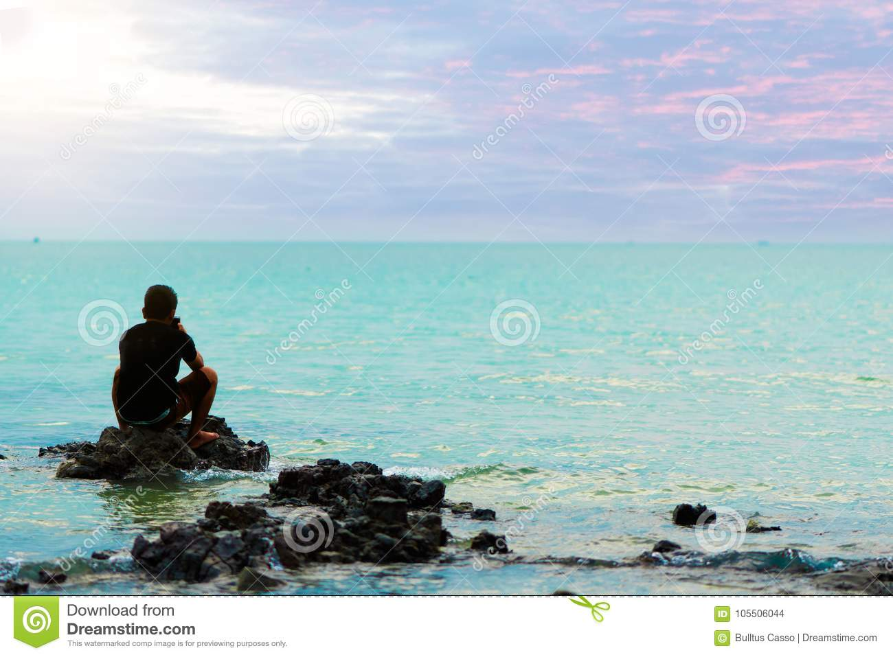Sad Man Sitting On Rock In The Sea Feeling Lonely And ...