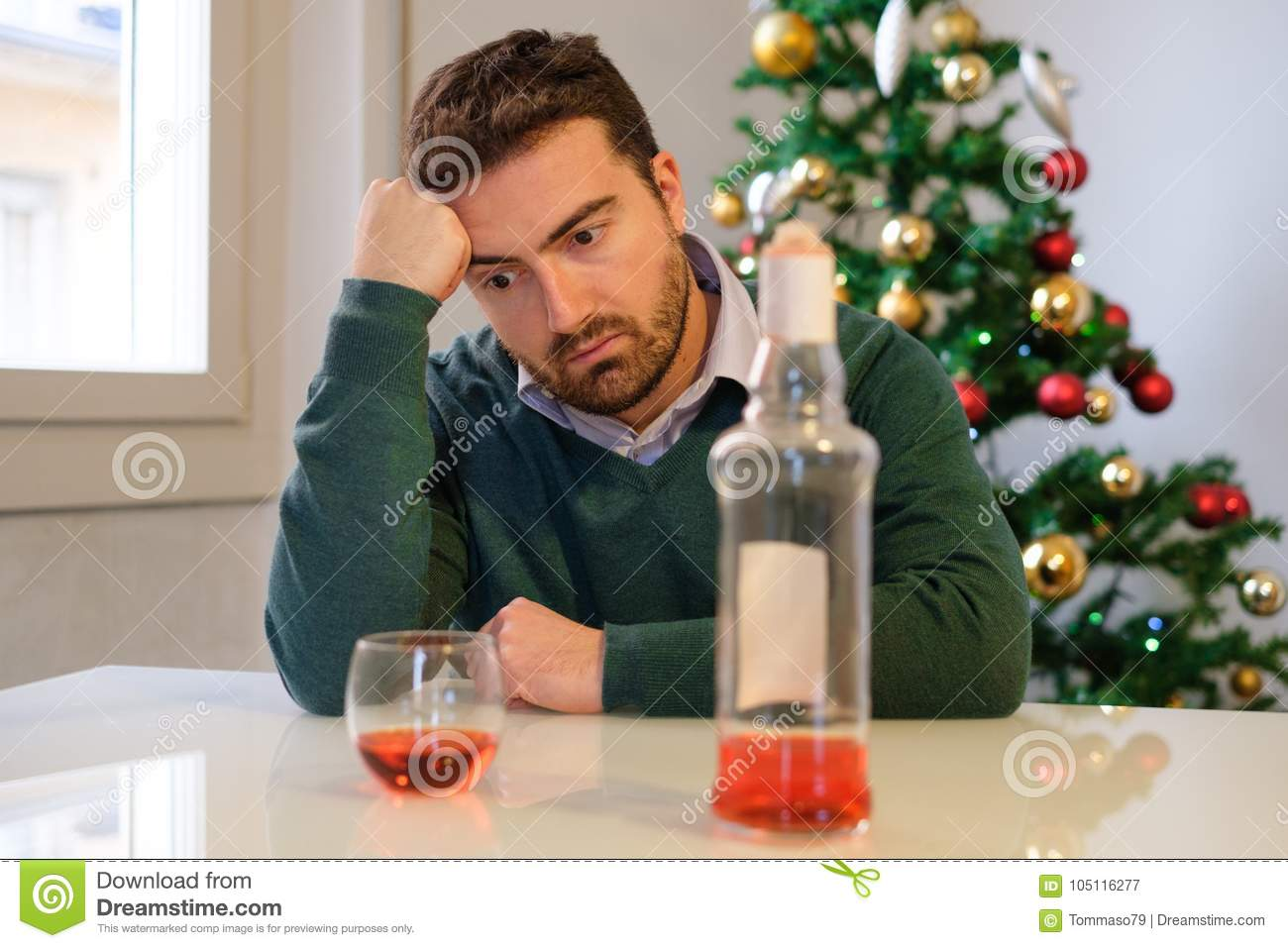 Alone For Christmas.Lonely Man Celebrating Christmas And Drinking Alone Stock
