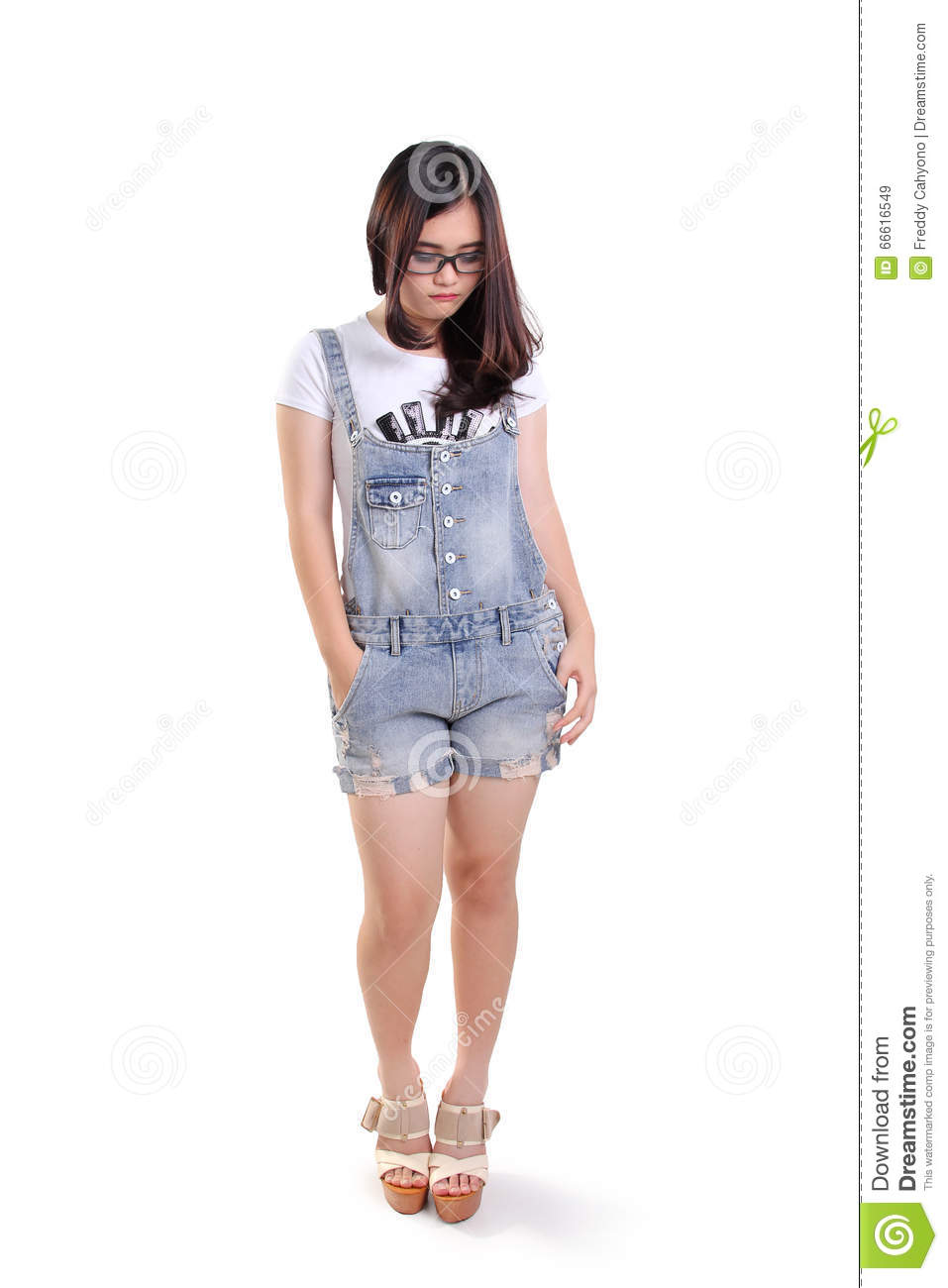 Full length portrait of cute sad nerdy girl looking down on white background