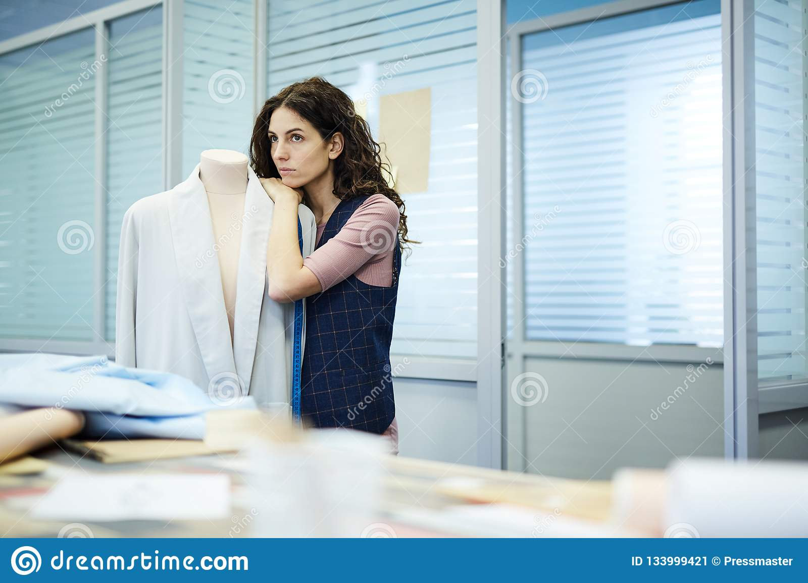 Sad pensive female tailor leaning on mannequin