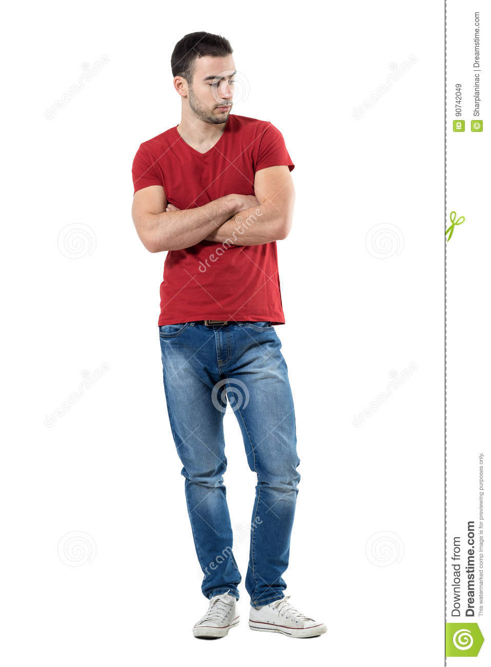 Sad pensive young man with crossed arms looking down