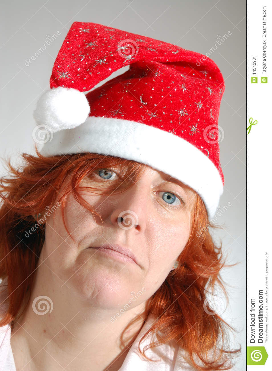 Up portrait of a sad lone middle aged woman with a red santa hat