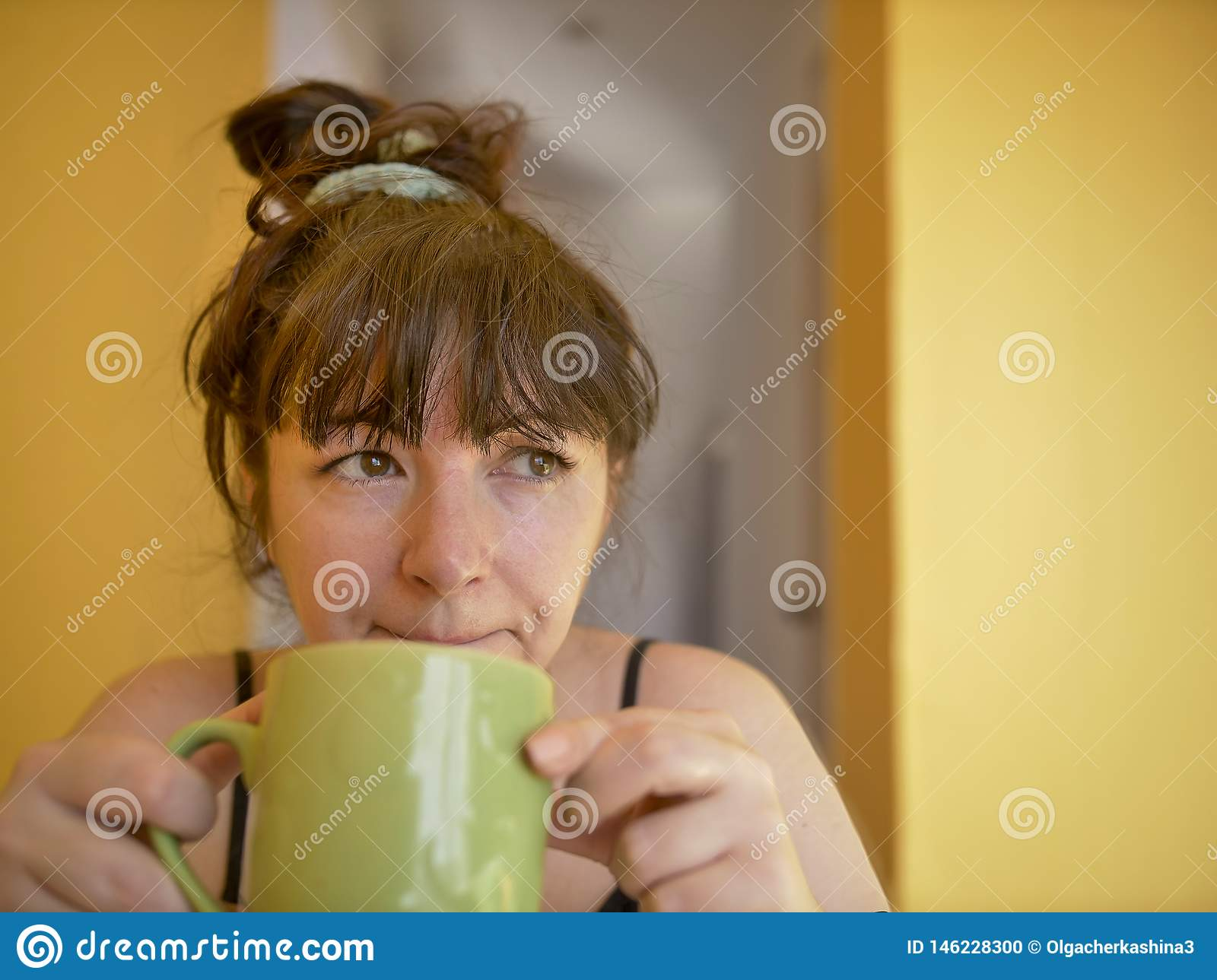 Sad and sleepy young woman with a cup of coffee in the morning at home