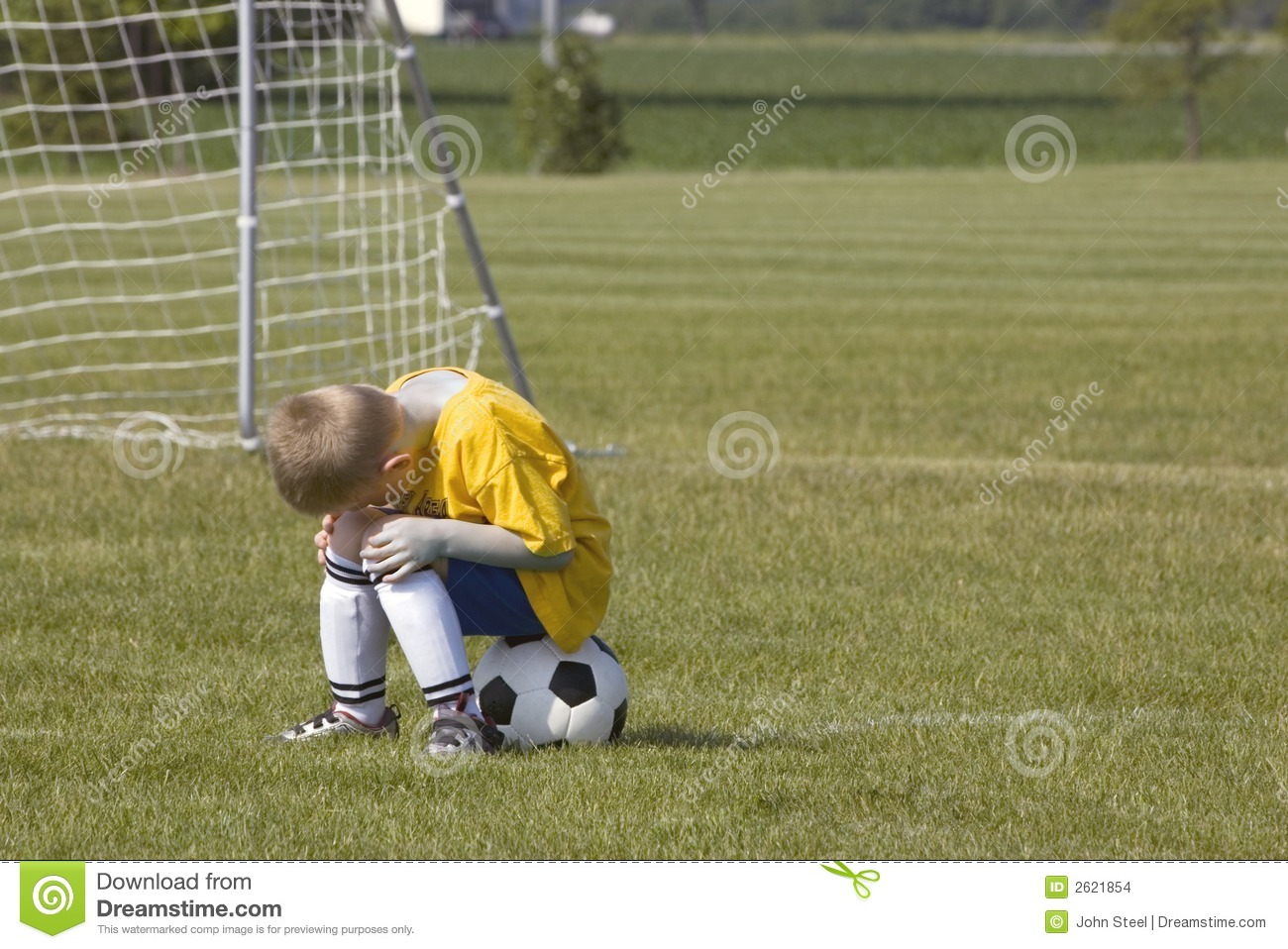Here is a photo of a young boy sitting on a soccer ball. He is ...
