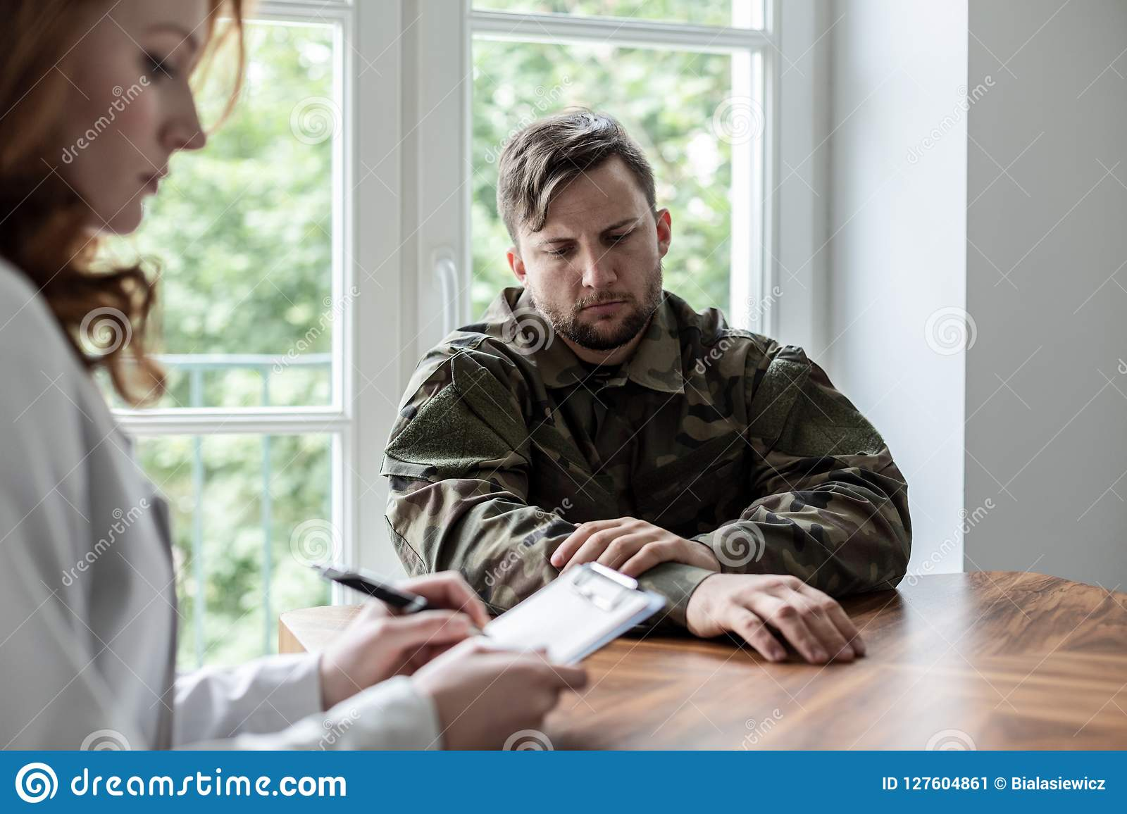 Sad soldier with depression and war syndrome during therapy with psychiatrist