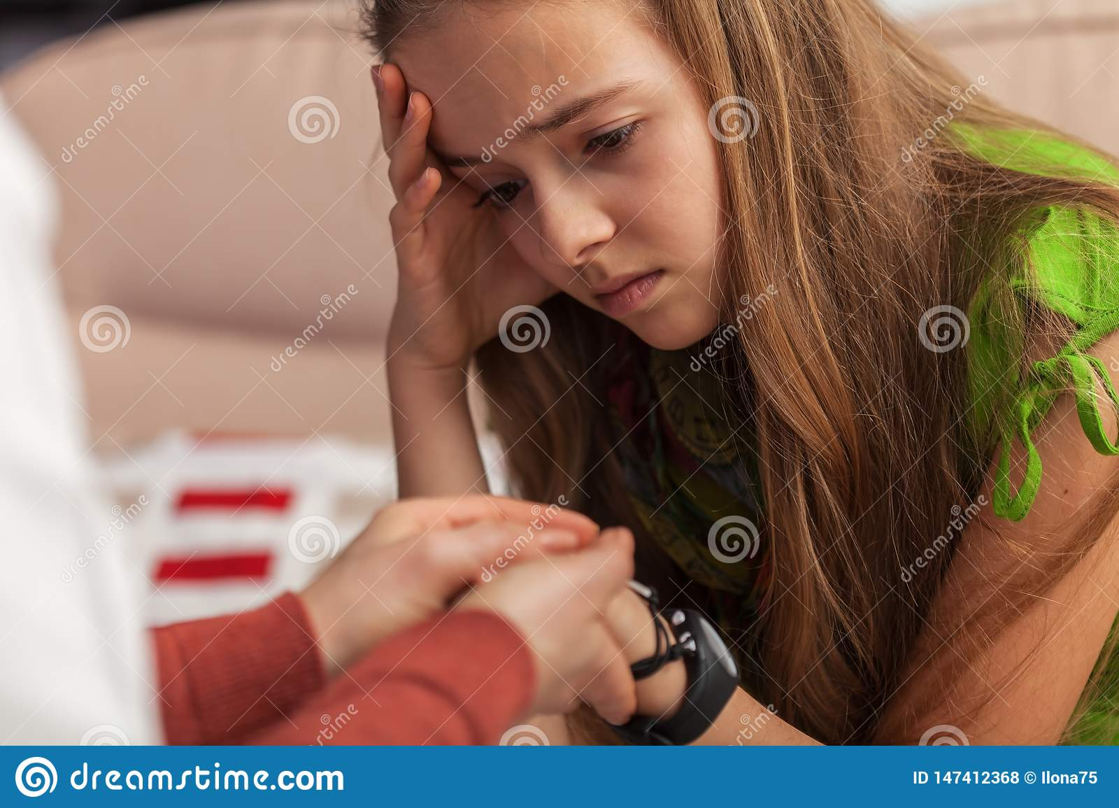 Sad teenager girl at counseling - woman professional hands holding and comforting young girl