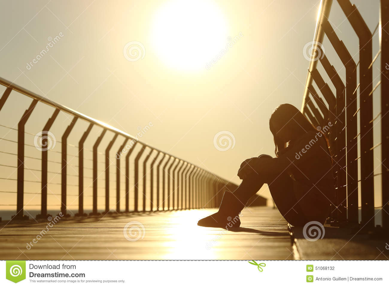 Sad teenager girl depressed sitting in a bridge at sunset