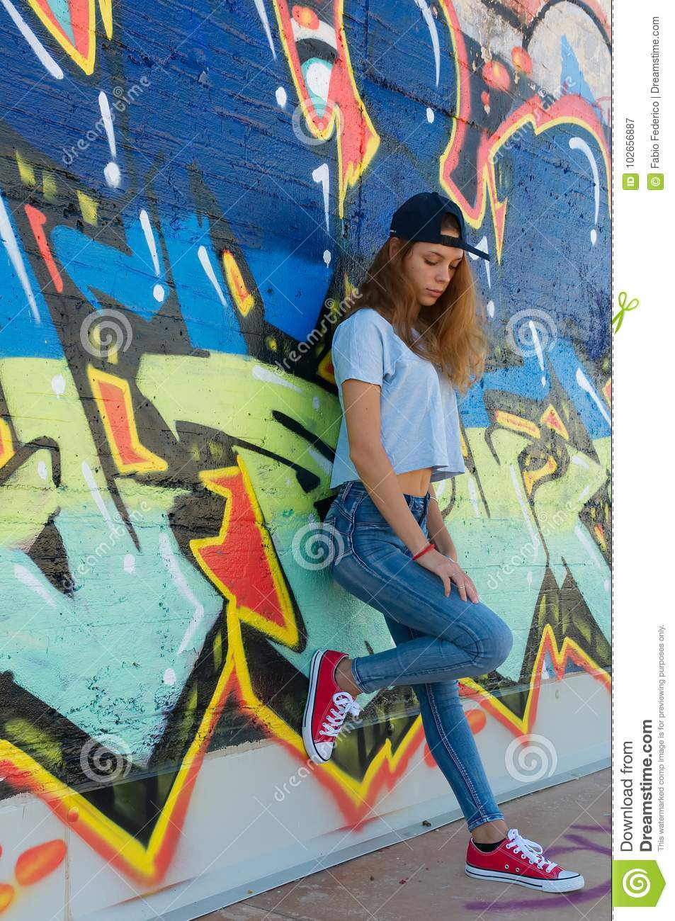Sad teenager leaning against a graffiti wall
