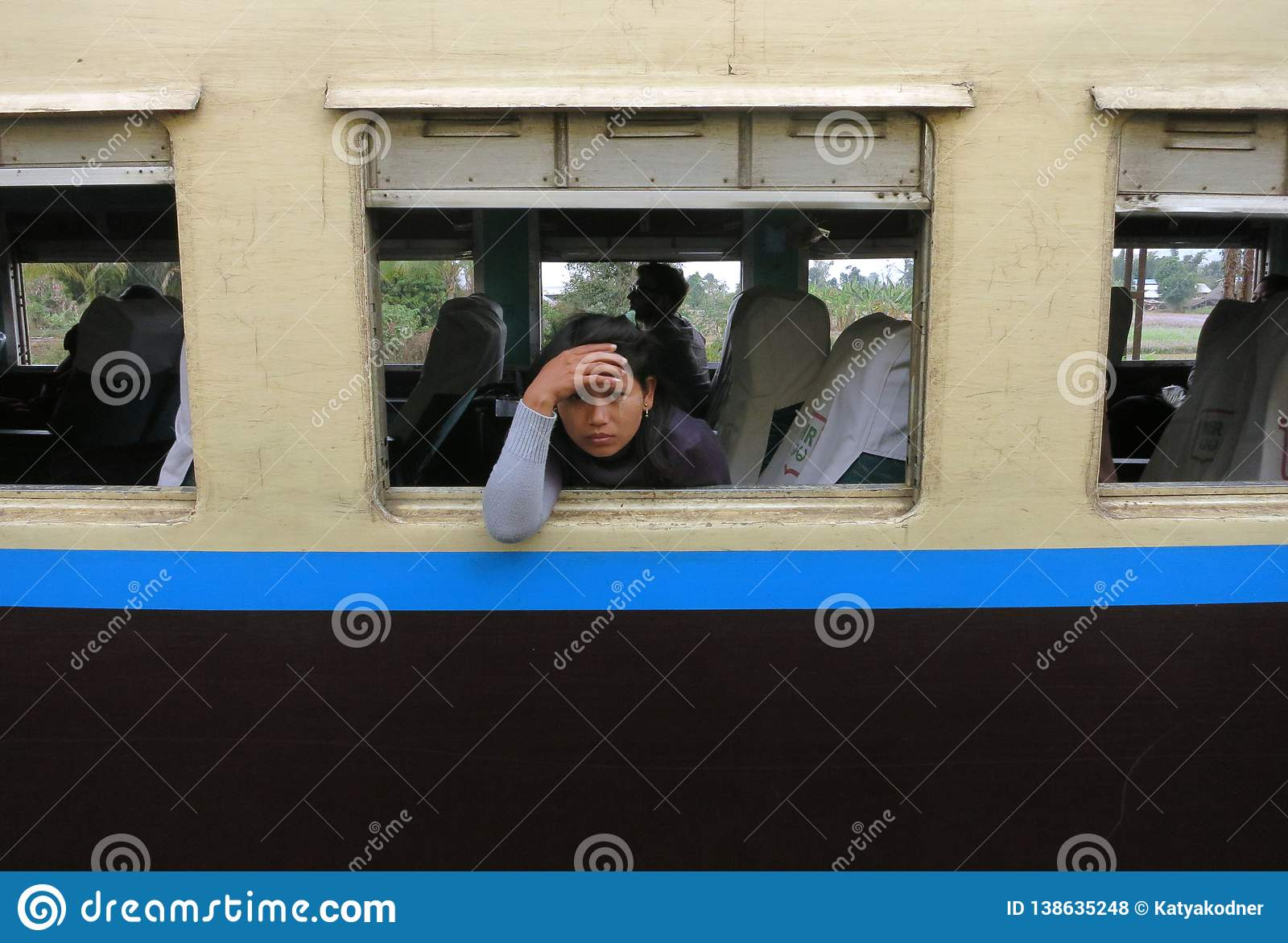 A sad and tired Burmese girl looking out of the window of an old train