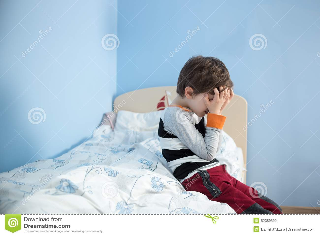 sad upset little boy sitting on the edge of his bed stock image image 52389599. Black Bedroom Furniture Sets. Home Design Ideas