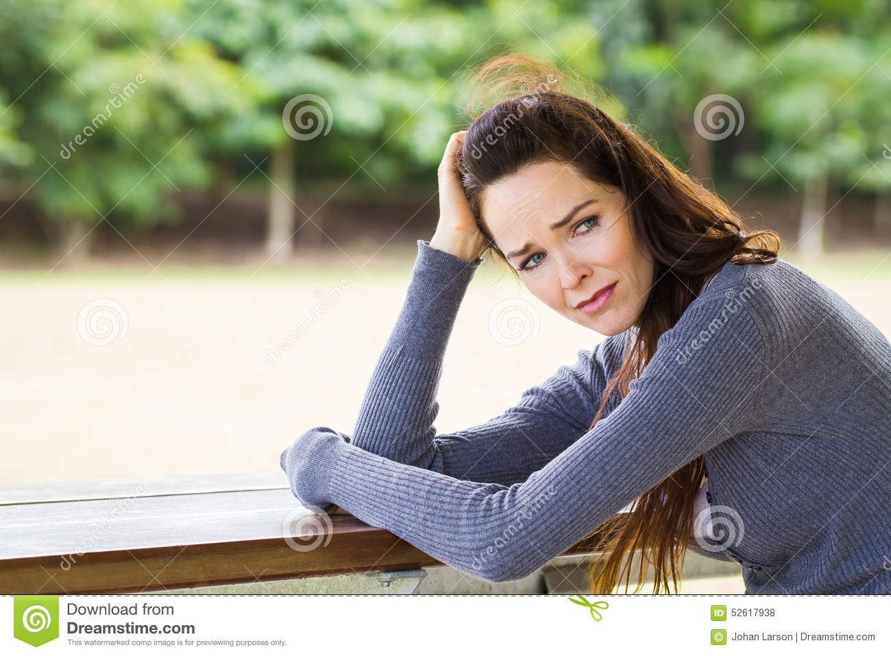Sad, upset and worried woman sitting outdoors