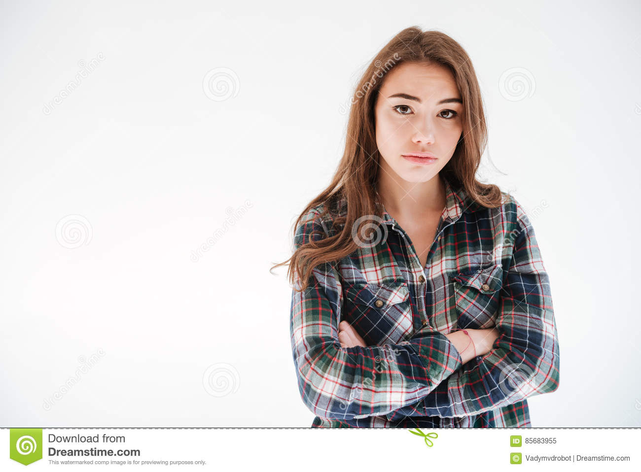 b6274109 Sad upset young woman in plaid shirt standing with arms crossed over white  background