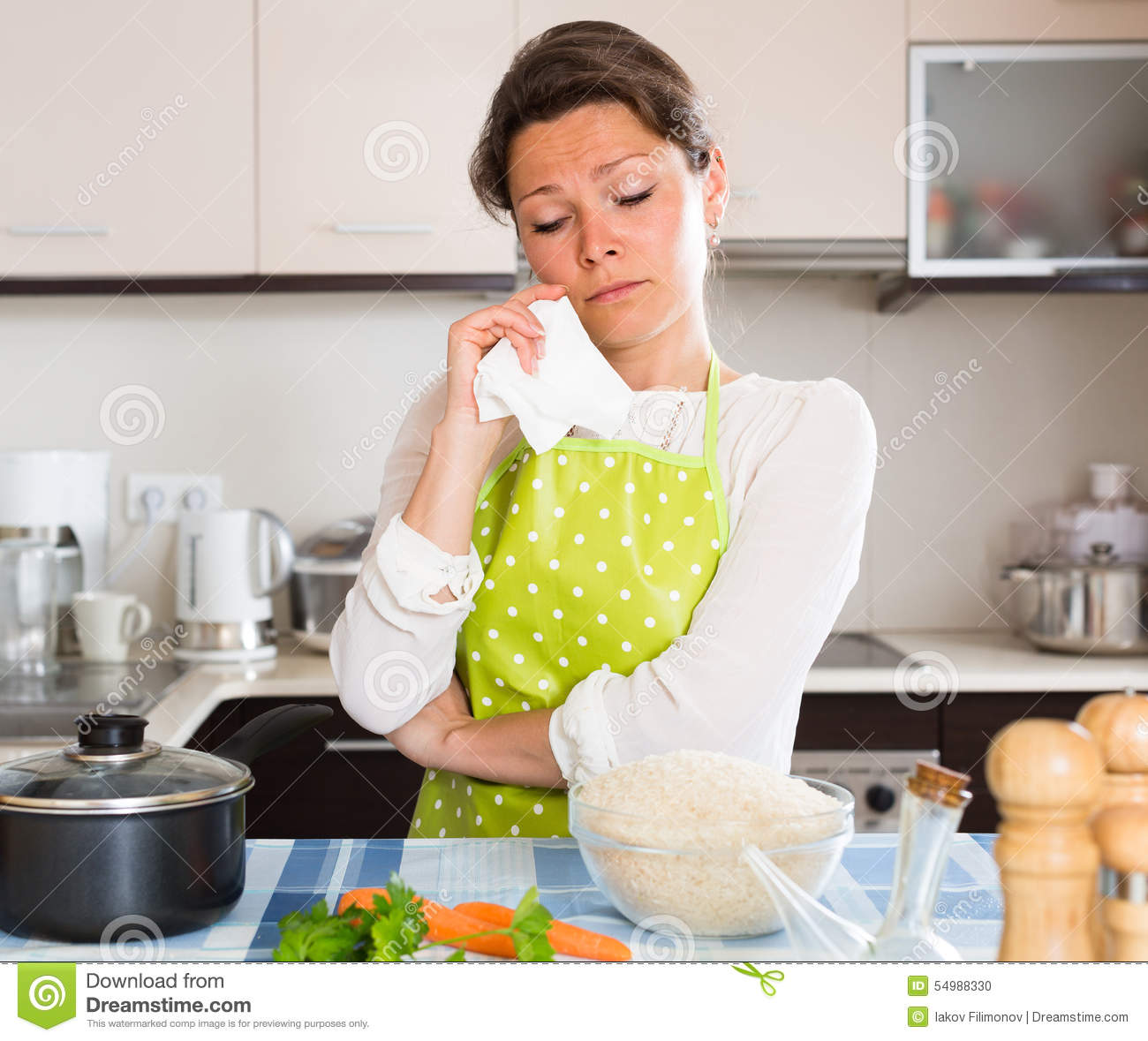 Sad woman cooking rice in the kitchen