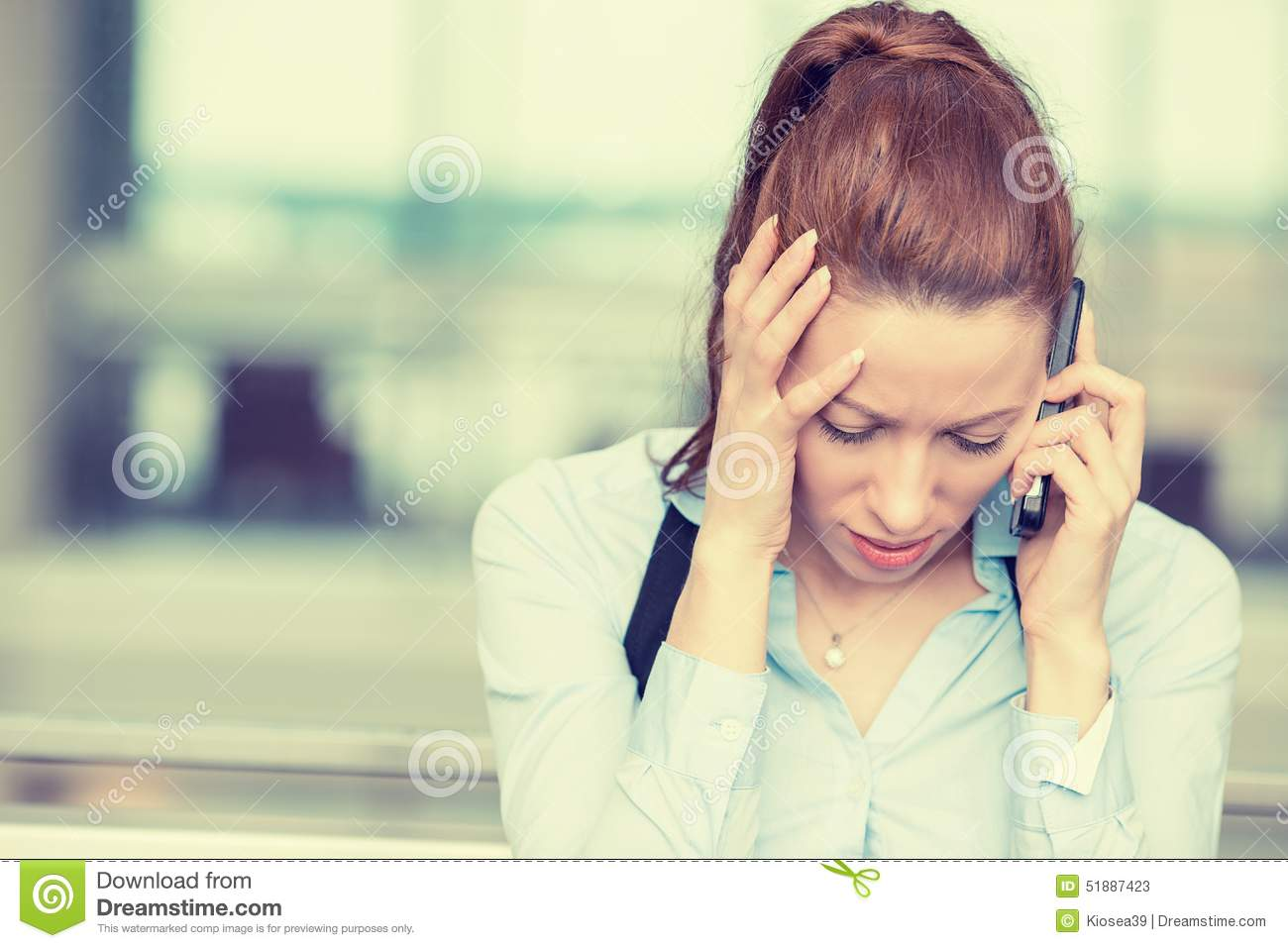 Sad woman talking on mobile phone looking down