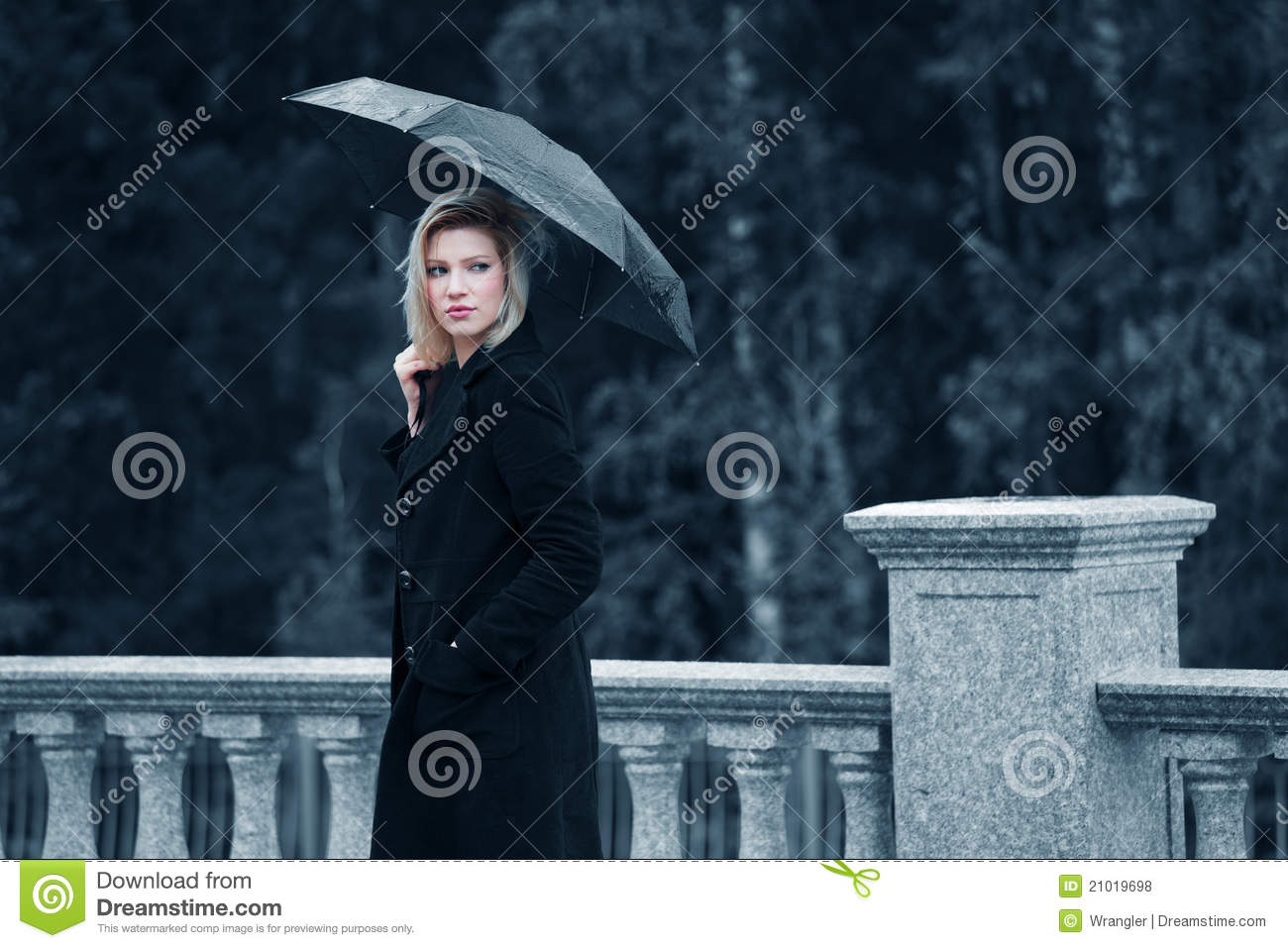 Sad young fashion woman with umbrella walking outdoor