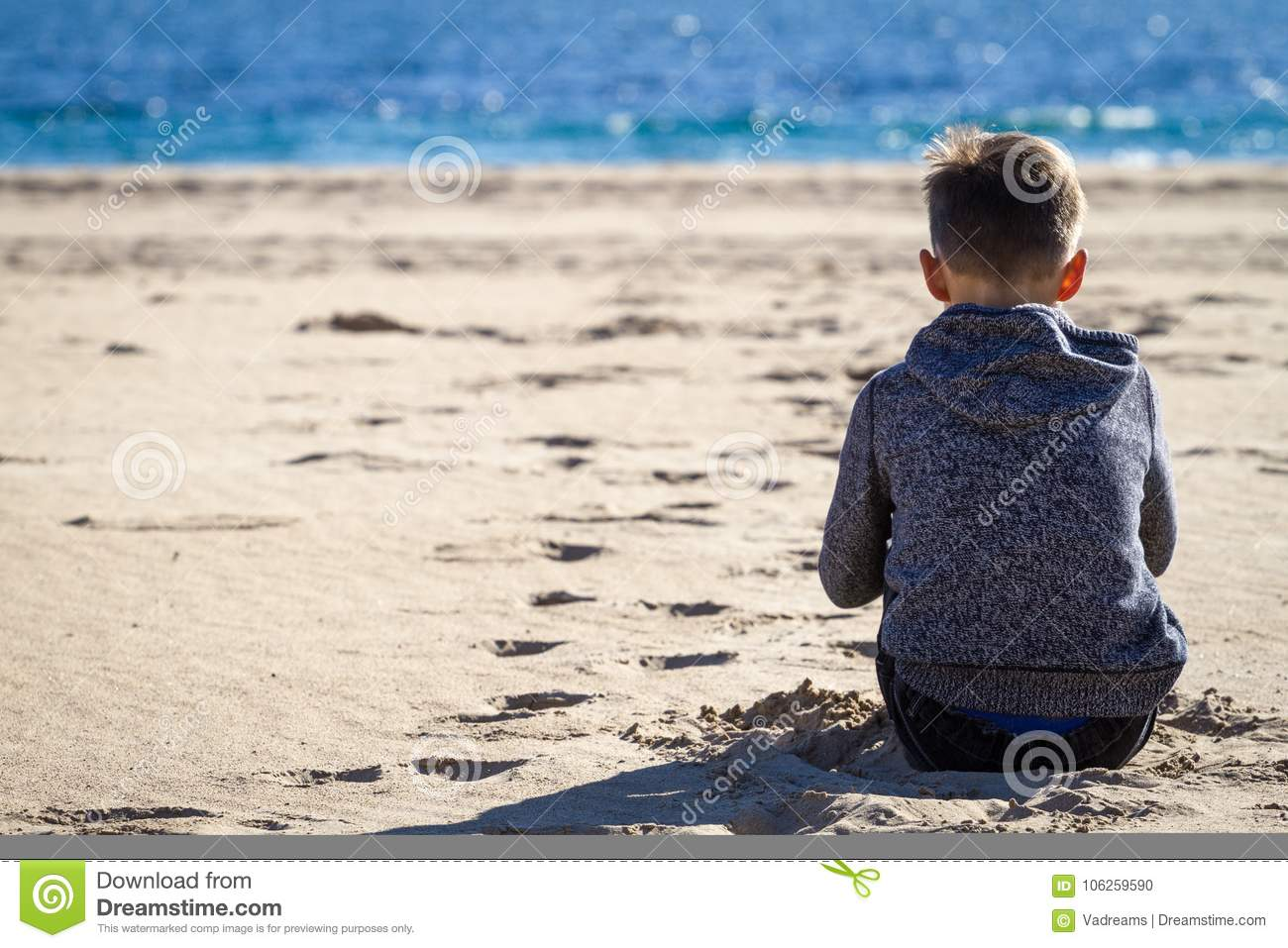 Sad alone boy sitting on the beach looking at sea and thinking