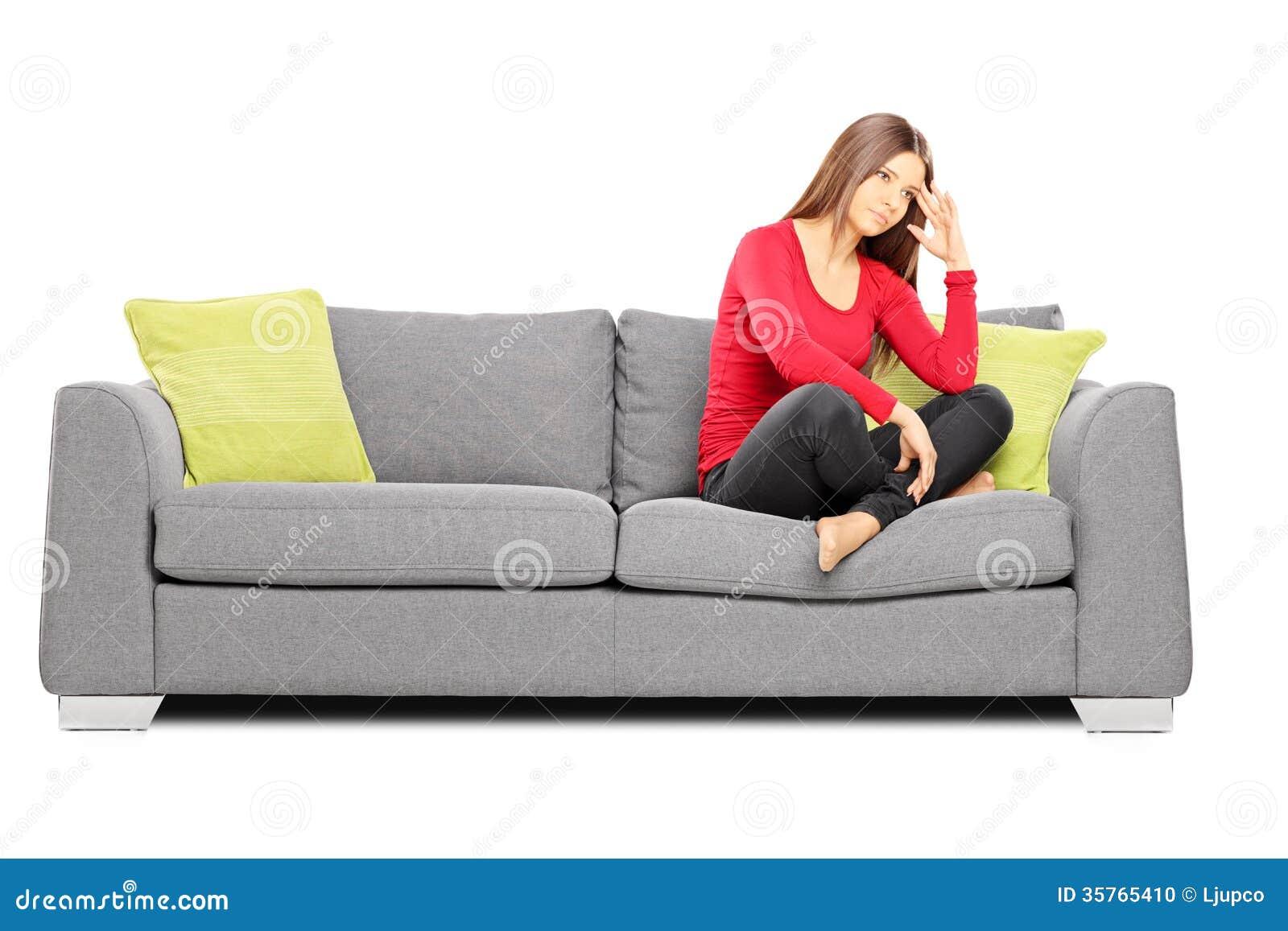 sad young female sitting on a sofa stock photo image. Black Bedroom Furniture Sets. Home Design Ideas