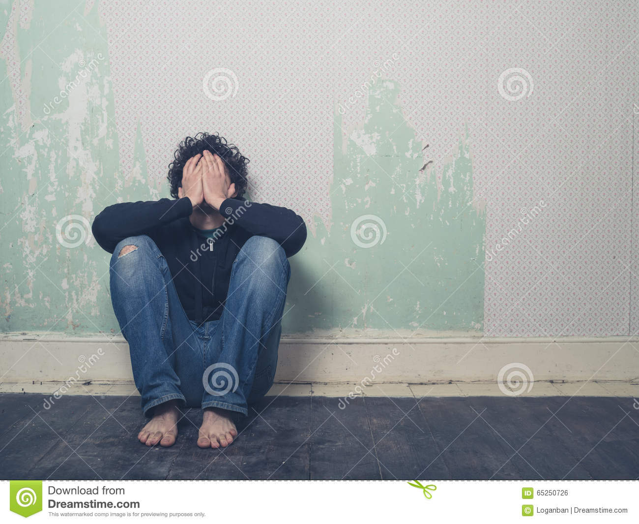 Sad young man in empty room