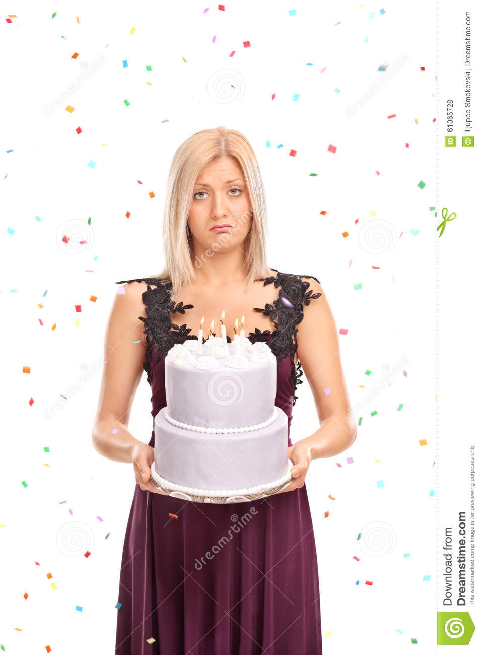 Sad young woman holding a birthday cake