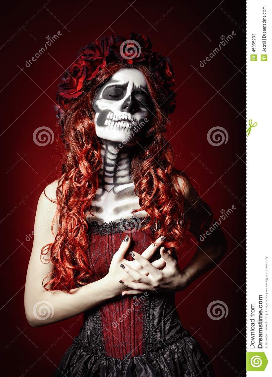 Sad young woman with muertos makeup (sugar skull) holding her chest