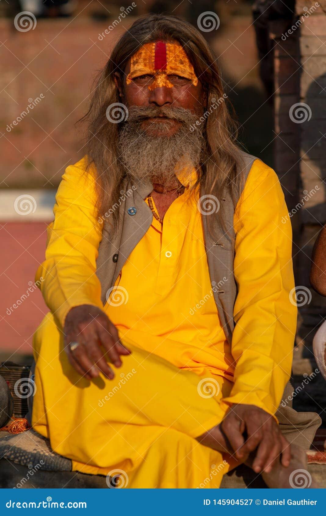 Saddhu com a camisa longa do algodão amarelo do açafrão, templo de Pashupatinath