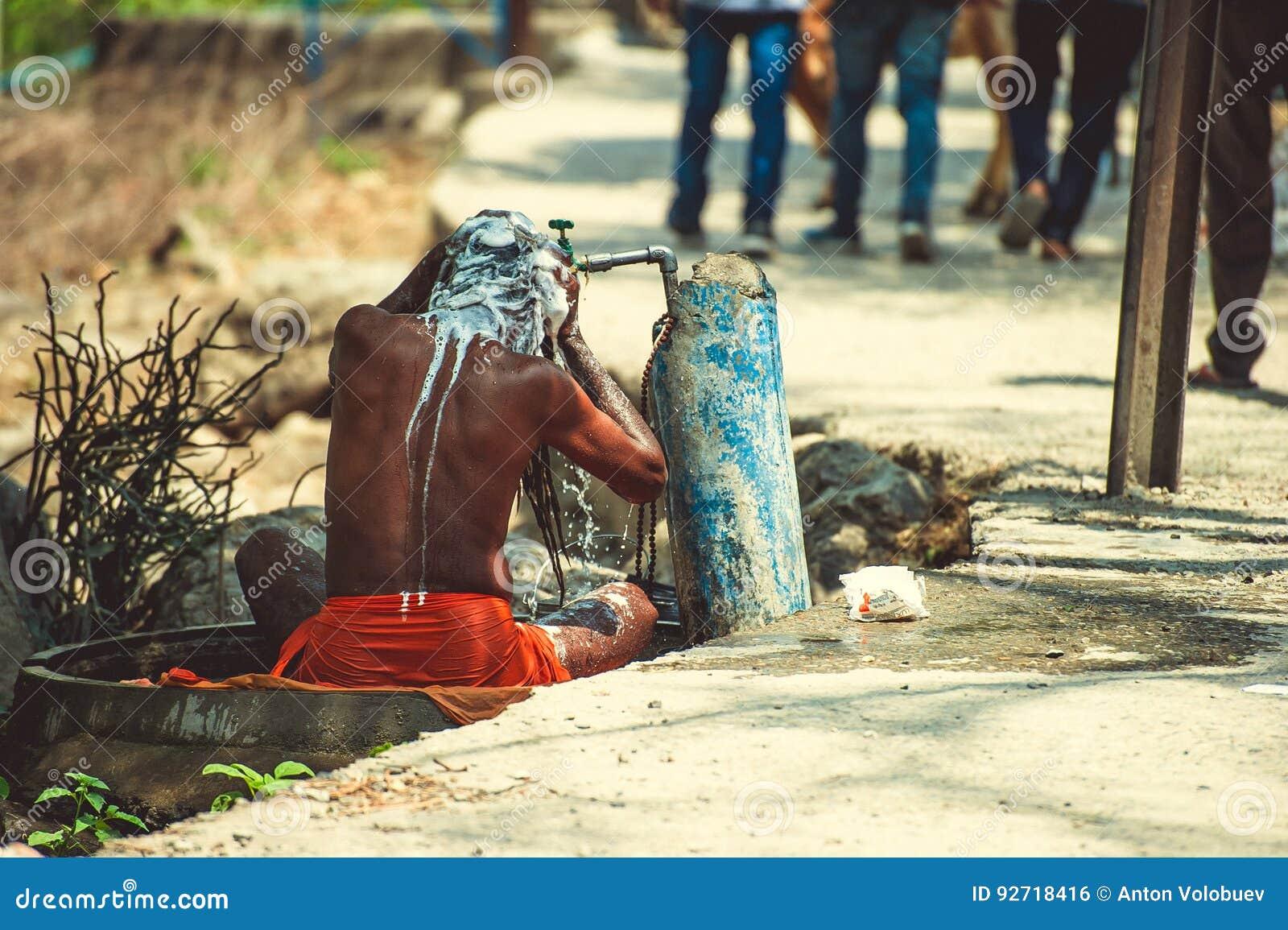 Sadhu è lavato sotto acqua corrente vicino alla strada