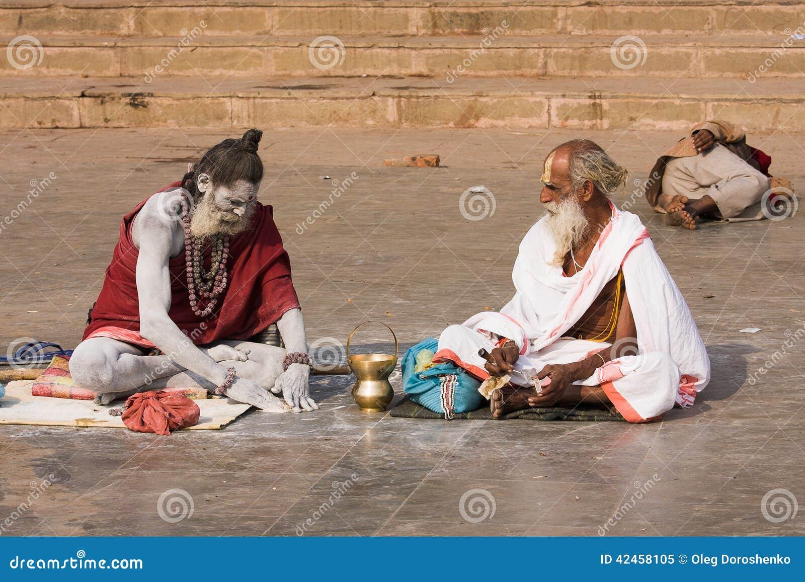 Sadhu sitzt auf dem ghat entlang dem Ganges in Varanasi, Indien