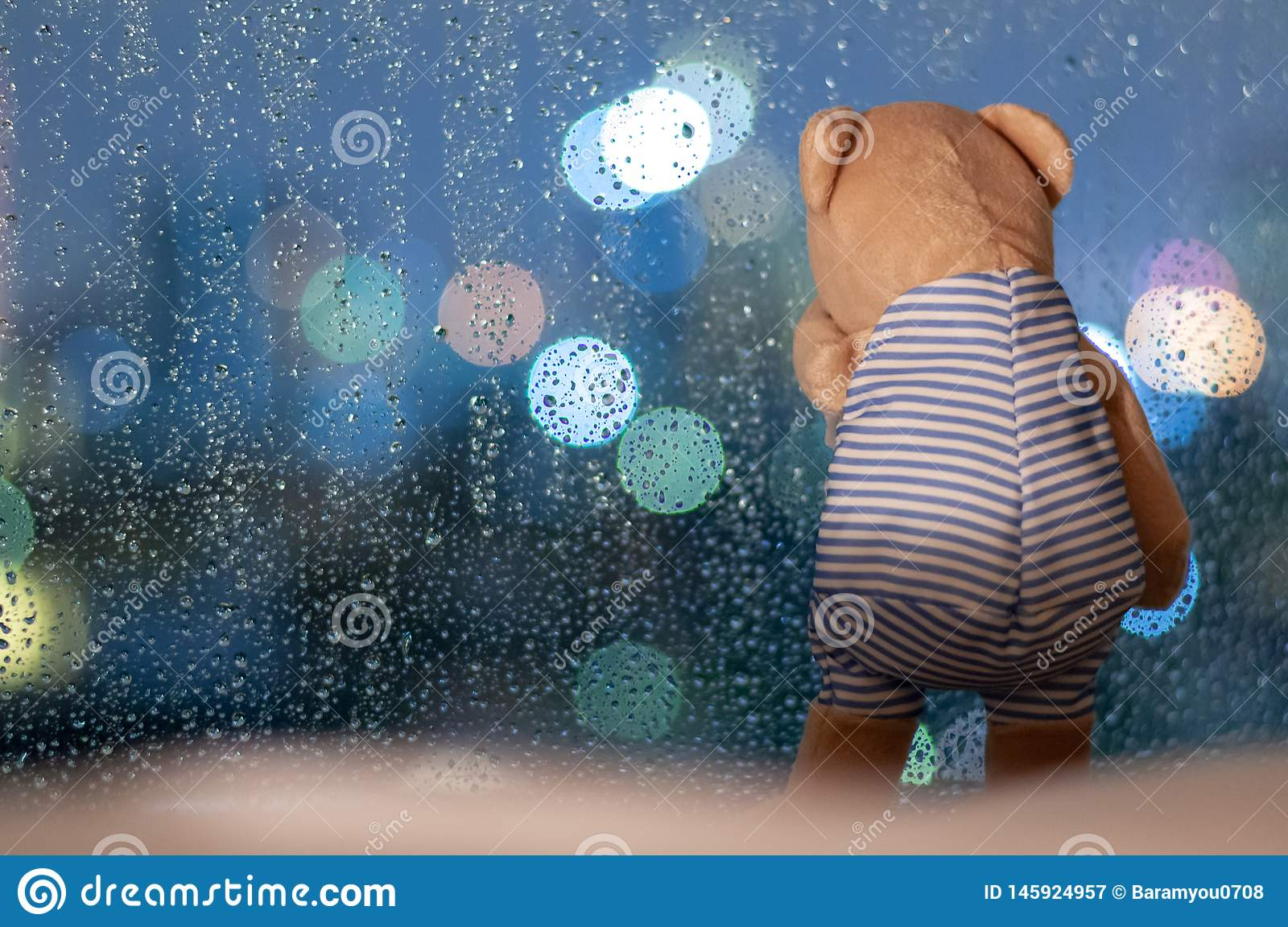 Sadly Teddy Bear crying at window in rainy day
