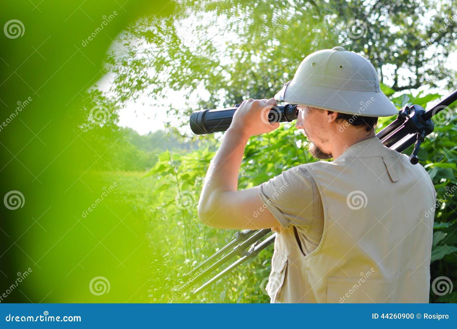 Safari turnerar: bild av den manliga turisten eller den undersökande forskaren i kärnahjälmen som har gyckel observera att se i f