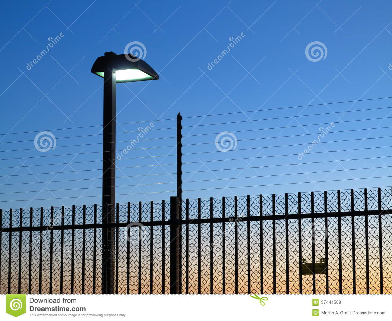 Safety fence with spotlight on by dusk royalty free stock