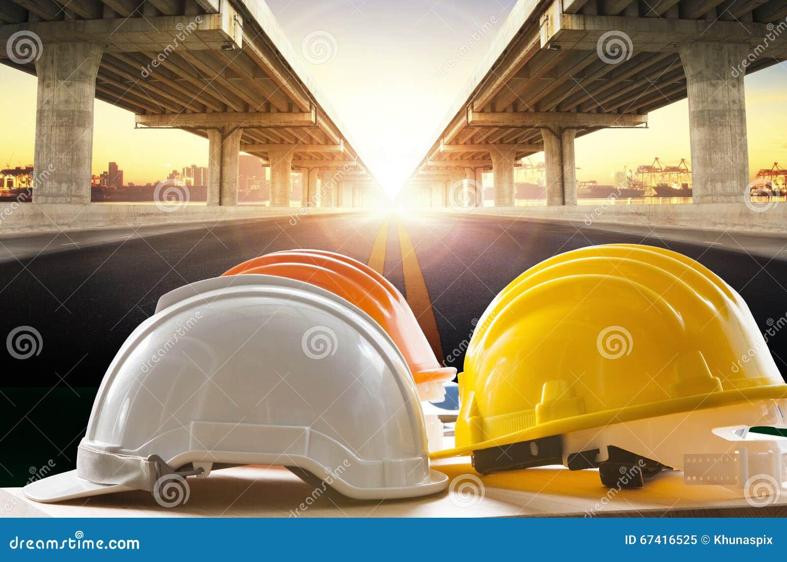 Safety helmet on civil engineering working table against bridge