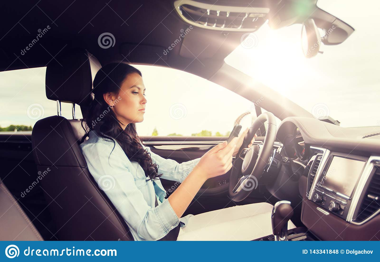Woman driving car with smarhphone