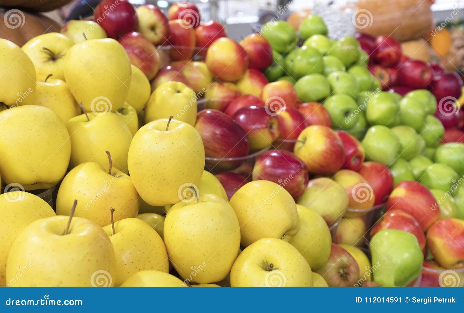 Saftig äpplebakgrund av guling, röd grön frukt som är till salu på marknaden