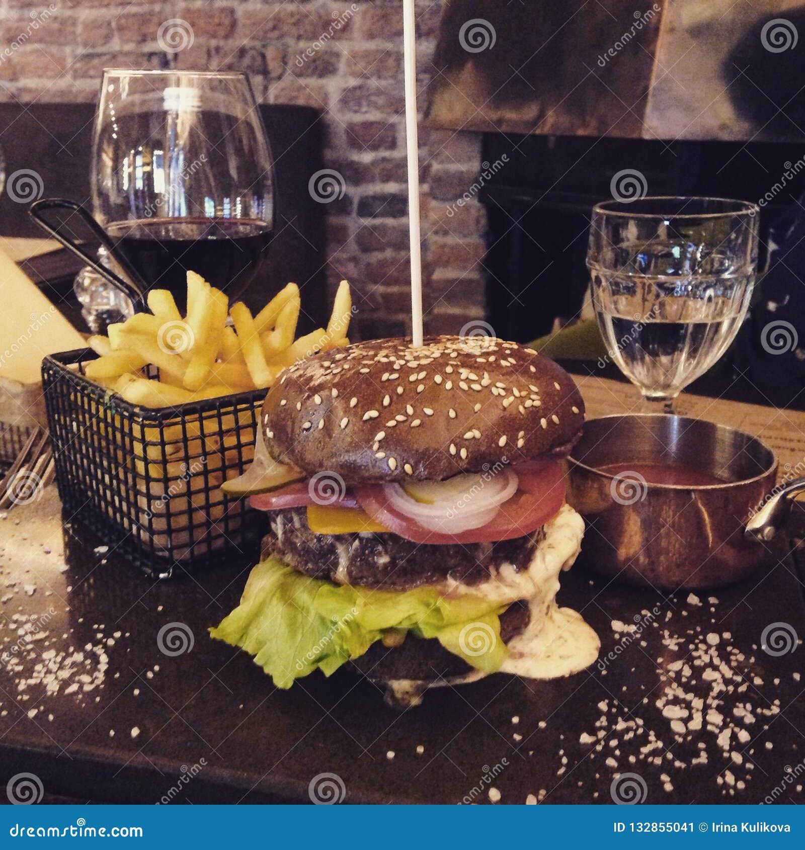 Saftig hamburgare med kött, grönsaker och ost på en tabell