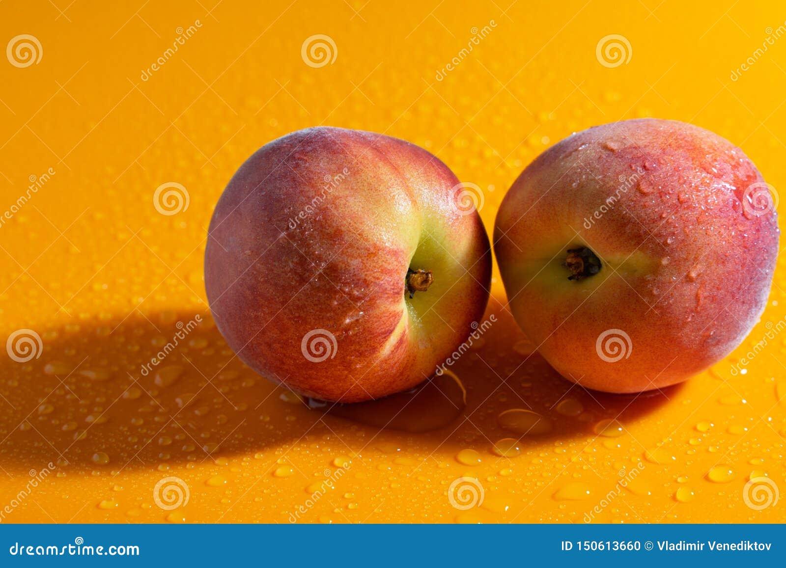 Saftig ny mogen persika på en orange matte bakgrund med vattendroppar frukter och sund mat