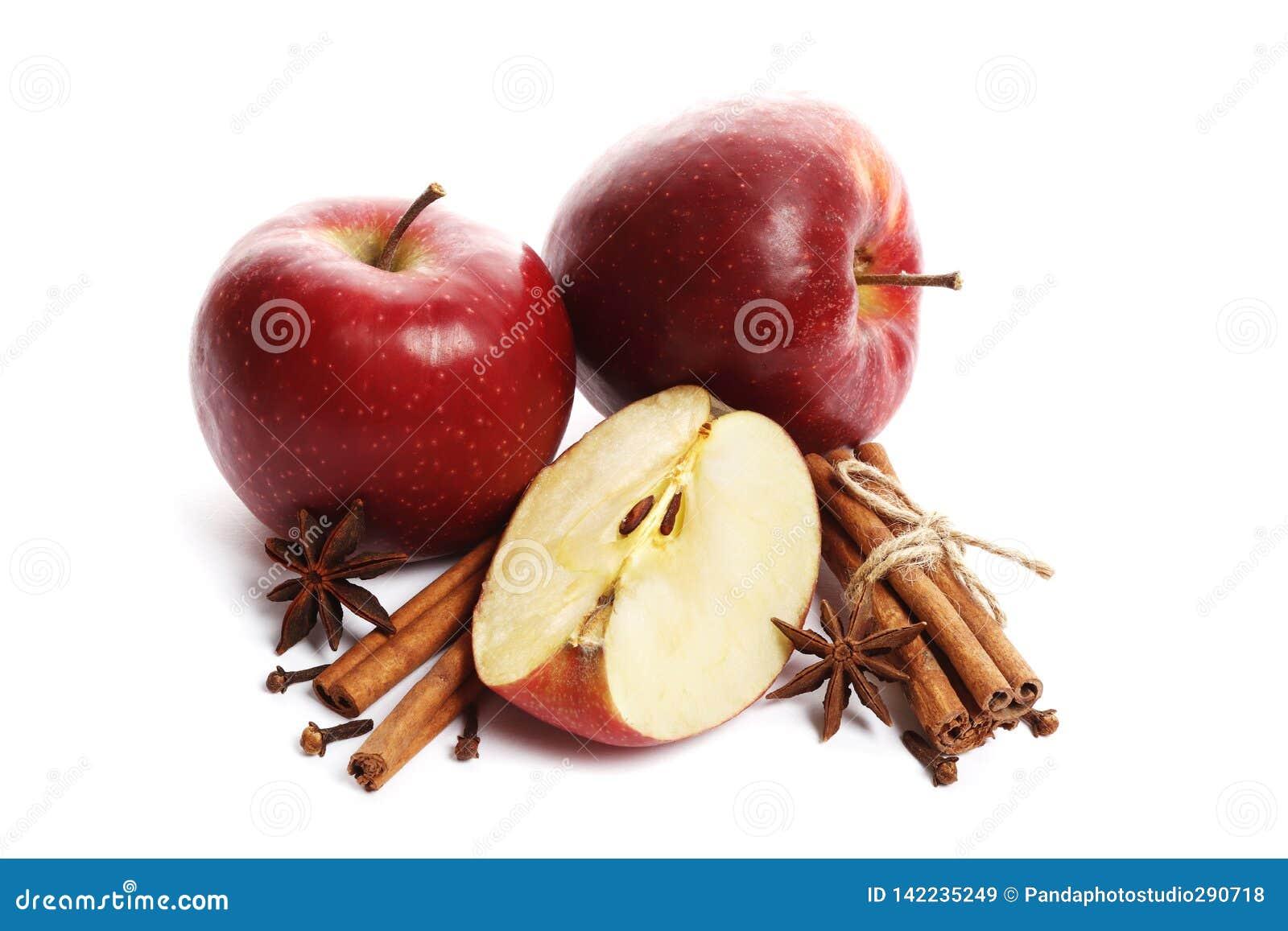 Saftige reife Äpfel mit dem Zimt- und Sternanis lokalisiert auf weißem Hintergrund