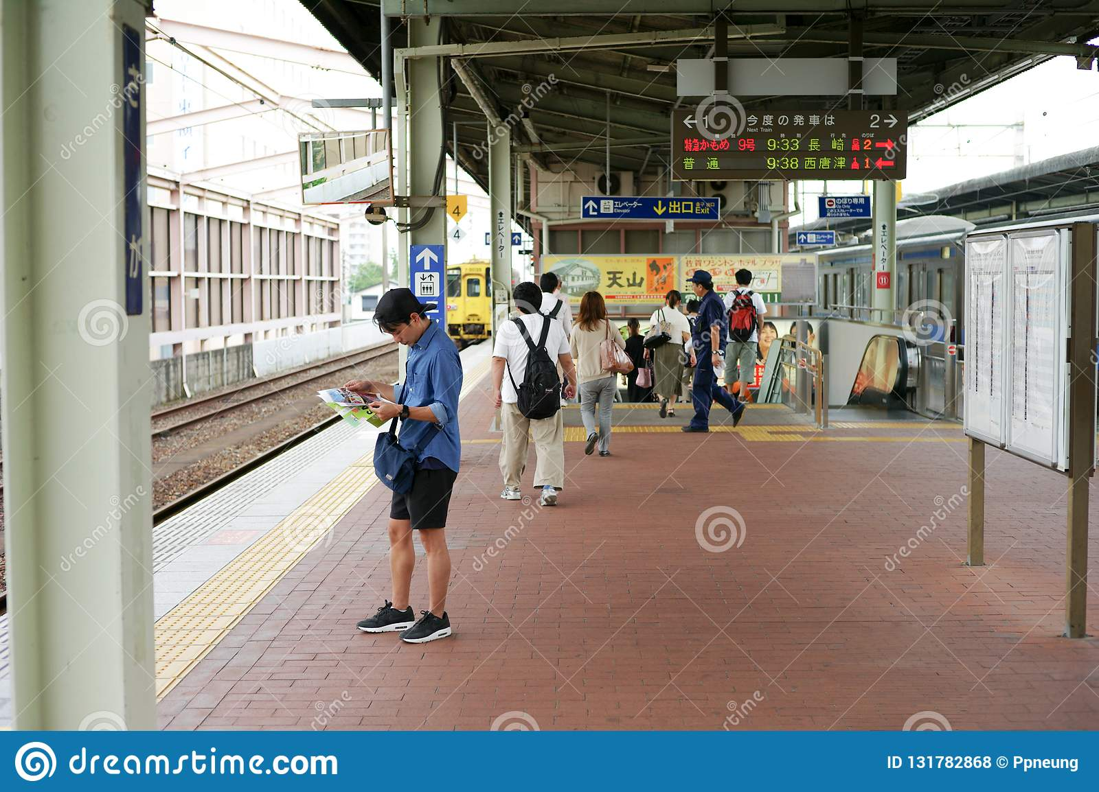 Saga, Japan:September 1, 2016 - Portrait Asian man standing and reading the map at the platform of the train station during