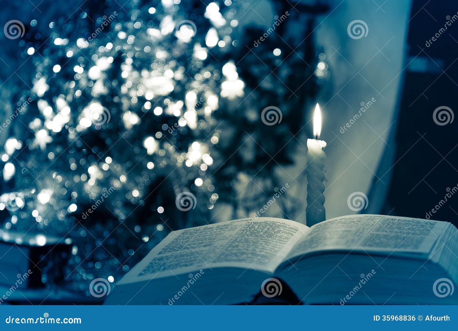 Sagrada Biblia con la vela en bokeh