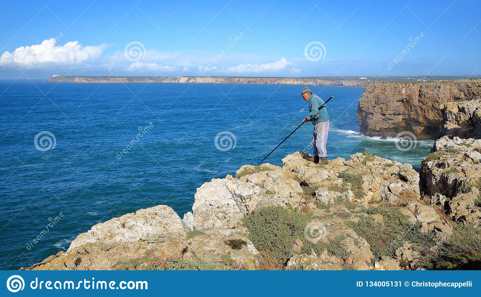 Fisherman angling above the high cliffs at Sagres Fortress Fortaleza with Cabo de Sao Vicente lighthouse in the background