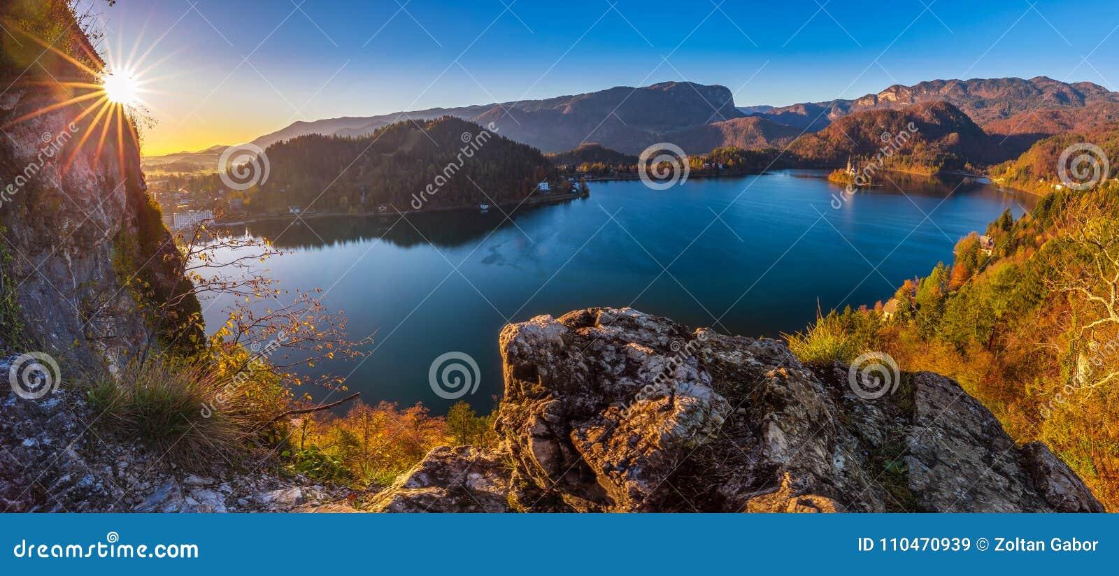 Saigné, la Slovénie - le beau lever de soleil d automne au lac a saigné sur un tir panoramique avec l église de pèlerinage de l a