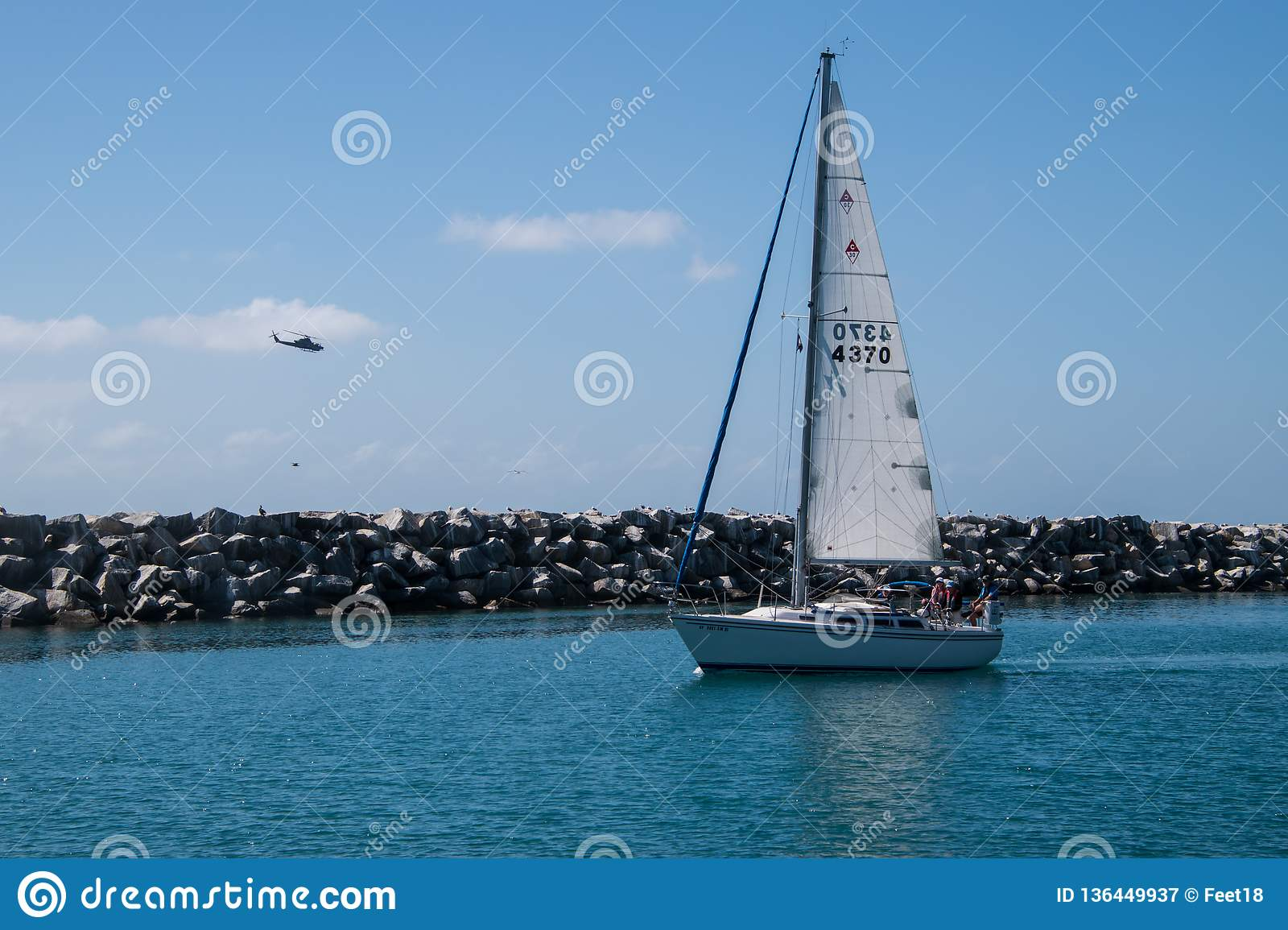 Sail Boat Carrying Four Passengers On Blue Green Water With