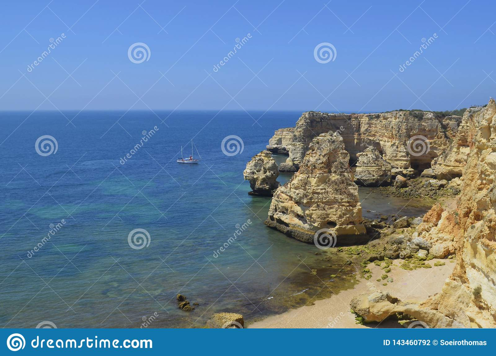Sailboat on deserted beach and cliffs