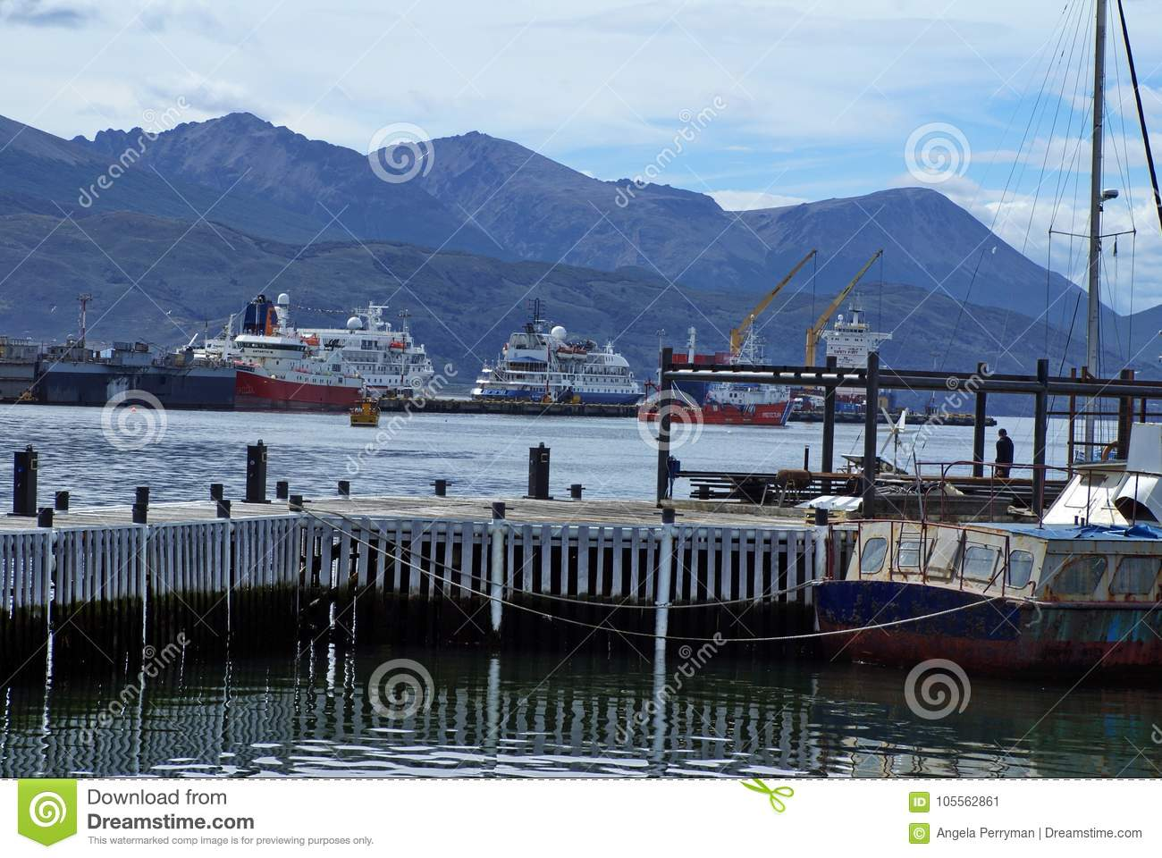 Sailboat at a wooden pier in Ushuaia Harbor with the commercial pier in the background