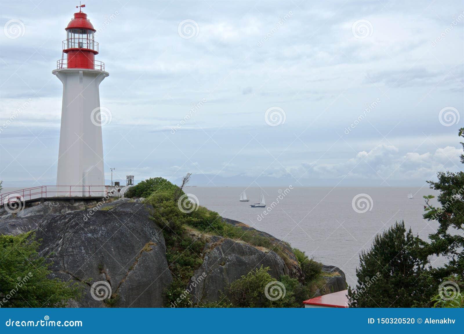Sailboats στη θάλασσα και το φάρο στο seacoast βράχο