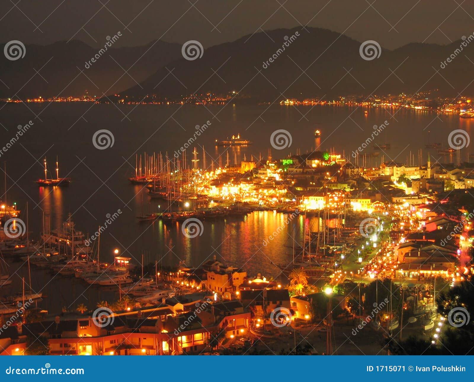 Sailboats anchored in harbor night scene