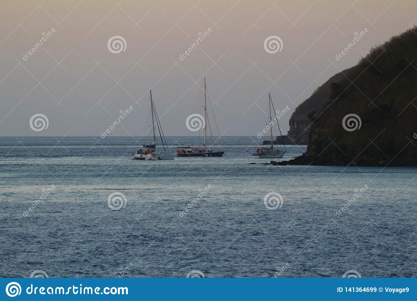 Sailboats anchored at nightfall in a bay of a tropical island, Fiji