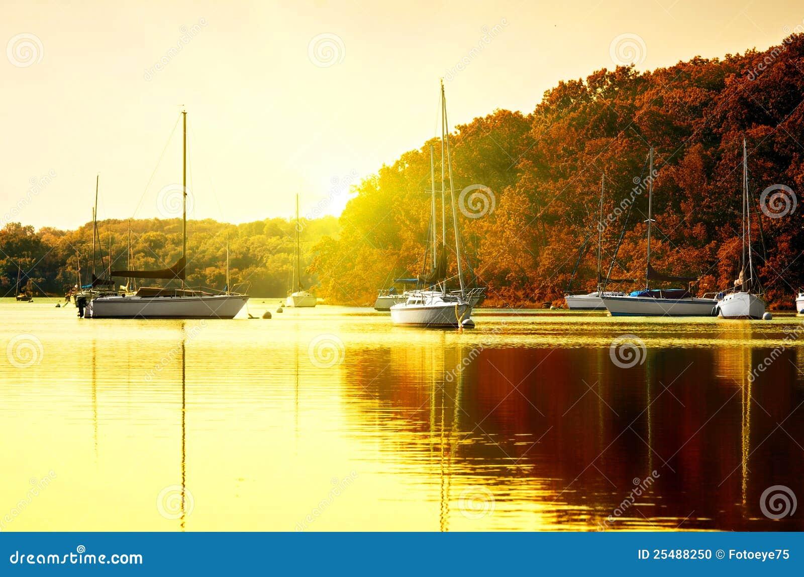 Sailboats no lago no por do sol