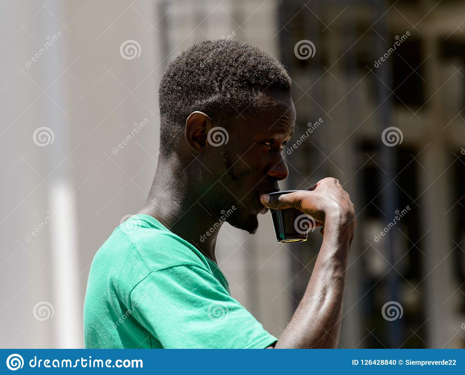 Unidentified Senegalese man holds a plastic cup in the centre o