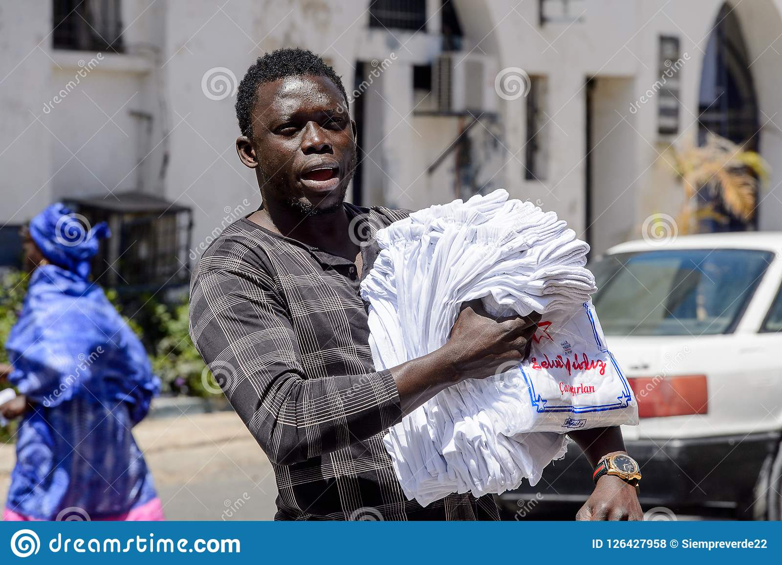 Unidentified Senegalese man walks along the street with goods f